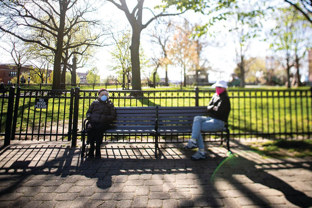 A picture of two people socially distancing on a park bench in Federal Hill by sitting far apart from eachother.