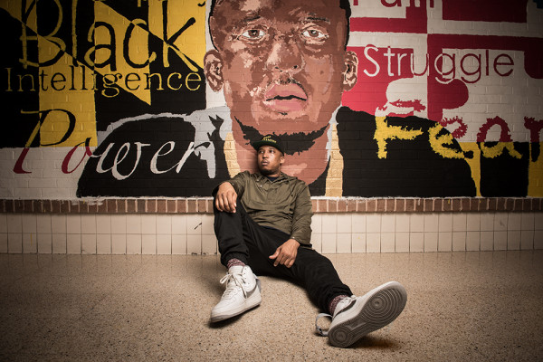 Watkins and a mural of his likeness, painted by students at Reach! Partnership School.Photography by Mike Morgan