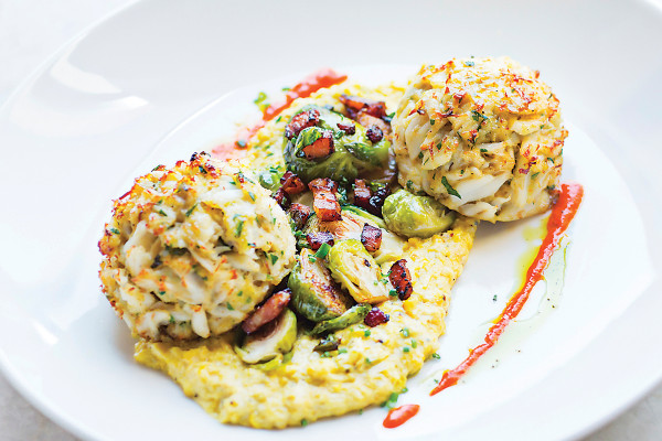 Crab cakes atop sweet corn and roasted Brussels sprouts.Photo by Scott Suchman