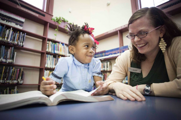Librarian Meredith Veatch reads with 5-year-old McKenzie at Enoch Pratt's Patterson Park branch.Courtesy of Enoch Pratt Free Library
