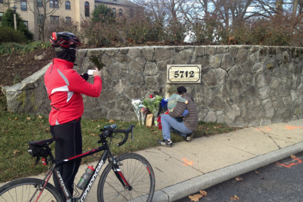 Bicyclists and friends continue to place flowers near the scene of the crash.—Photo by Ron Cassie