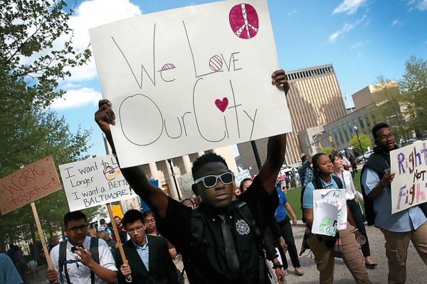 """On April 29, 2015, students from Digital Harbor High School carry homemade signs and chant, """"We love Baltimore"""" as they march outside City Hall.Win McNamee/Getty Images"""